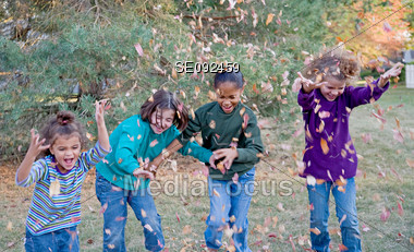 Girls Playing in the Fall Leaves Stock Photo