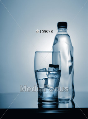 Glass Of Cold Mineral Water With Ice And Plastic Bottle Stock Photo
