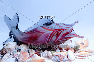 Glass Fish Lies On A Handful Of Shells. Stock Photo