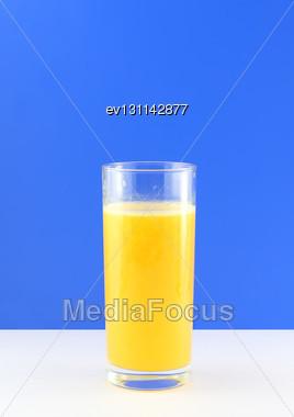 Glass Of Fresh Orange Juice With Squeeze Slice On Blue Background Stock Photo