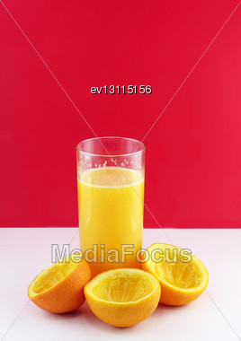 Glass Of Fresh Orange Juice With Squeeze Slice On Red Background Stock Photo