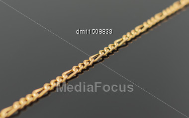 Gold Chain Lying On Black Table Stock Photo