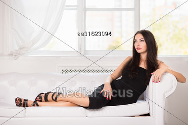 Gorgeous Brunette In Black Dress Posing On The White Sofa Stock Photo