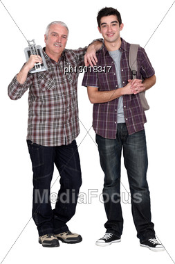 Grandfather Teaching His Grandson How To Lay Tiles. Stock Photo