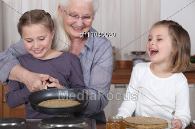 Grandmother And Granddaughters Making Pancakes Stock Photo