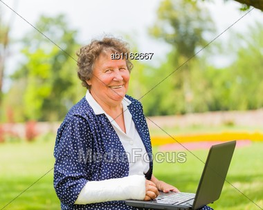 Grandmother With Bandage And Laptop Outdoors Using Social Network Stock Photo