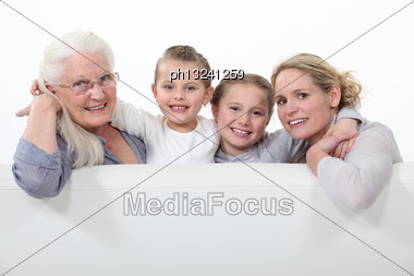 Grandmother, Mother And Daughters Behind White Sign Stock Photo