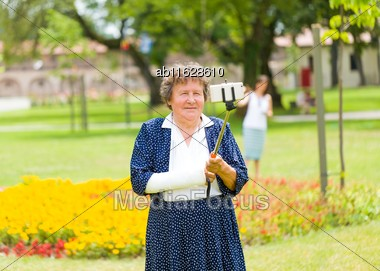 Grandmother With Trendy Dress And Bandage Holding Selfie Stick To Take Photo In The Floral Garden Stock Photo