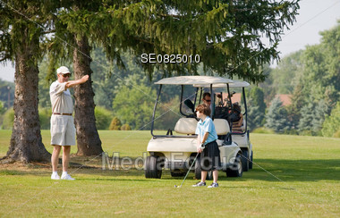 Grandpa Instructing Grandson in a Game of Golf Stock Photo