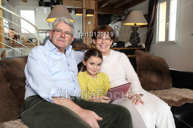 Grandparents And Granddaughter Using Laptop Computer Stock Photo