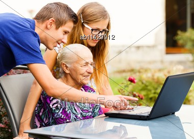 Grandson Showing Something To Grandma On The Computer Stock Photo