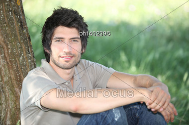 In The Grass, A Young Man Seated Against A Tree Stock Photo