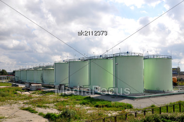 Greater Green Fuel Tanks On A Background Of Clouds Stock Photo