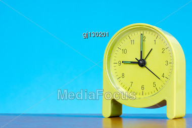 Green Alarm Clock On The Table Against Blue Background Stock Photo