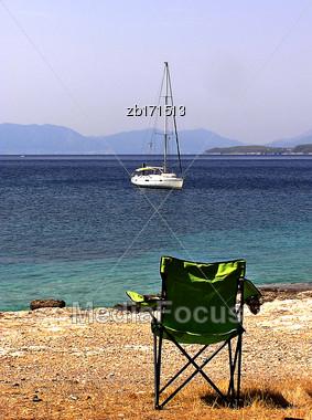 Green Beach Chair At Seashore And White Sailboat At Sunny Summer Day Stock Photo