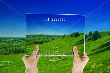Green Field In Hands On Nature Background Stock Photo