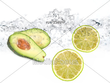 Green Limes And Avocado In Water Dropped Isolated On A White Stock Photo