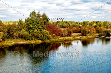Green, Red And Yellow Trees, The Reflections Of Trees In The Water, Roofs Of The House, The River Against The Blue Cloudy Sky Stock Photo