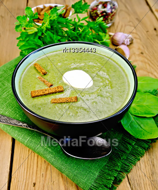 Green Soup Puree In A Bowl With A Spoon On A Napkin And Spinach, Parsley, Croutons, Garlic And Pepper On A Wooden Board Stock Photo