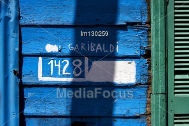 Green Wood Venetian Blind And A Blue Garibaldi Wall In La Boca Buenos Aires Argentina Stock Photo