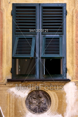 Green Wood Venetian Blind Statue And A Yellow Wall In The Centre Portofino Italy Stock Photo