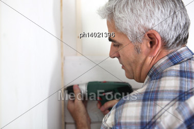 Grey Haired Handyman Drilling Into Wall Stock Photo