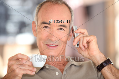 Grey Haired Man Drinking Coffee And Speaking On Mobile Telephone Stock Photo