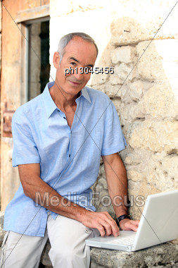 Grey Haired Man Sat By Stone Wall With Laptop Stock Photo