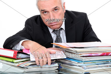 Grey Hairy Man Looking Fed Up In Front Of Paper Work Stock Photo