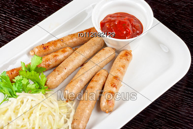 Grilled Sausages With Cabbage, Greens And Tomato Sauce On White Plate Stock Photo
