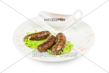 Grilled Venison Sausage On A White With Lettuce And Sauce Stock Photo