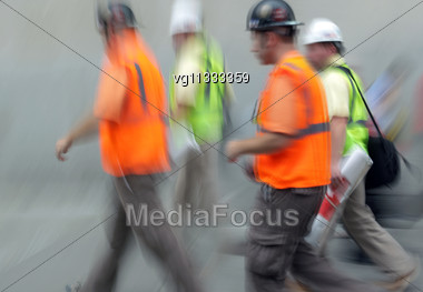 Group Of A Construction Workers Walking On The Street Blurred Motion Stock Photo