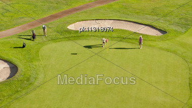 Group Of Golfers On A Putting Green Stock Photo