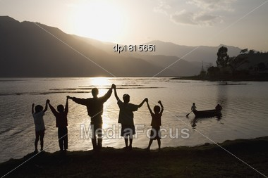 A Group Of People With Arms Raised Stock Photo