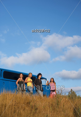 Group Of Young People Standing Next To A Bus Stock Photo