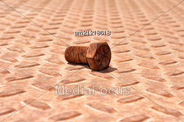 Grungy Background With A Rusty Ridged Metal Plate And Old Hexagonal Bolt Stock Photo