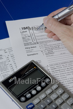 Hand Completing Tax Form 1040 Stock Photo