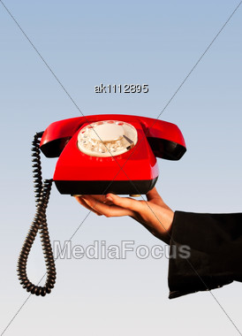 Hand Holding An Old Fashioned Red Phone Stock Photo