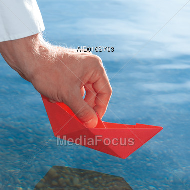 Hand Holding Red Origami Boat Over Water Stock Photo