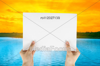 Hand Holding White Paper At Beauty Sunset On River Background Stock Photo