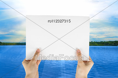 Hand Holding White Paper At Beauty Sunset On Sea Background Stock Photo