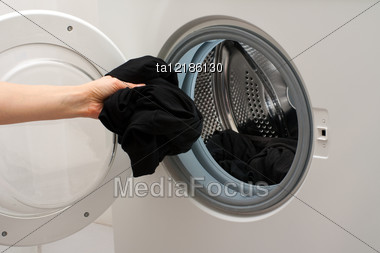 Hand Placing The Clothes In The Drum Of Washing Machine Stock Photo