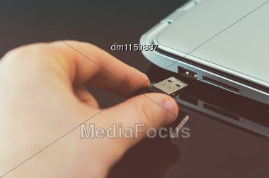 Hand Plugging Usb Flash Drive To Laptop Stock Photo