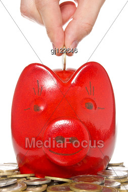 Hand Putting Coin Into The Red Piggy Bank Stock Photo