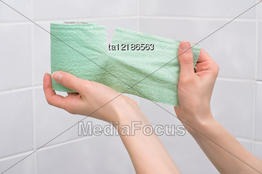 Hand Tears Off Green Toilet Paper On The Background Of Tiled Wall Stock Photo