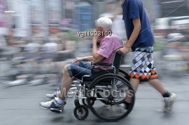 Handicapped Person On A Wheelchair With Assistant Stock Photo
