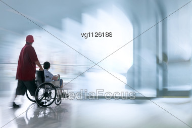 Handicapped Person On A Wheelchair With Assistant, Intentional Motion Blur Stock Photo