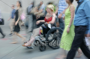 Handicapped Person On A Wheelchair With Assistant , People Walking By Stock Photo