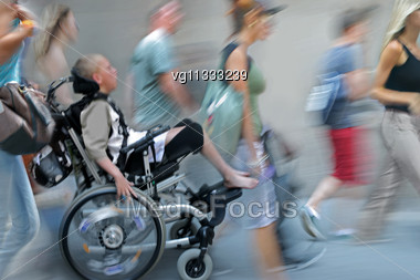 Handicapped Person On A Wheelchair On A Hot Summer Day In Motion Blur, Diverse People Walking By Stock Photo