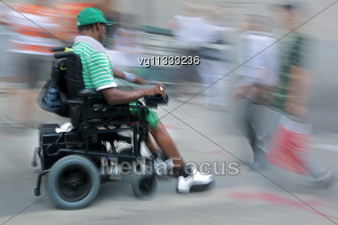 Handicapped Person On A Wheelchair In Motion Blur, Walking People Passing By Stock Photo
